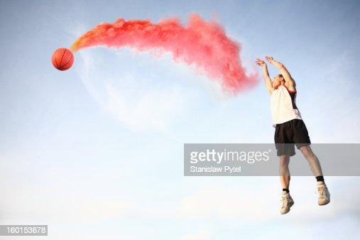 Basketball player throwing smoking ball : Bildbanksbilder