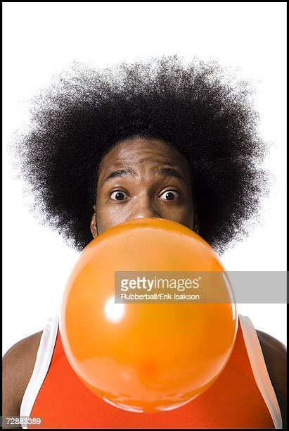 Basketball player with an afro blowing a bubble