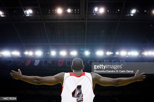Basketball player with arms outstretched, rear view