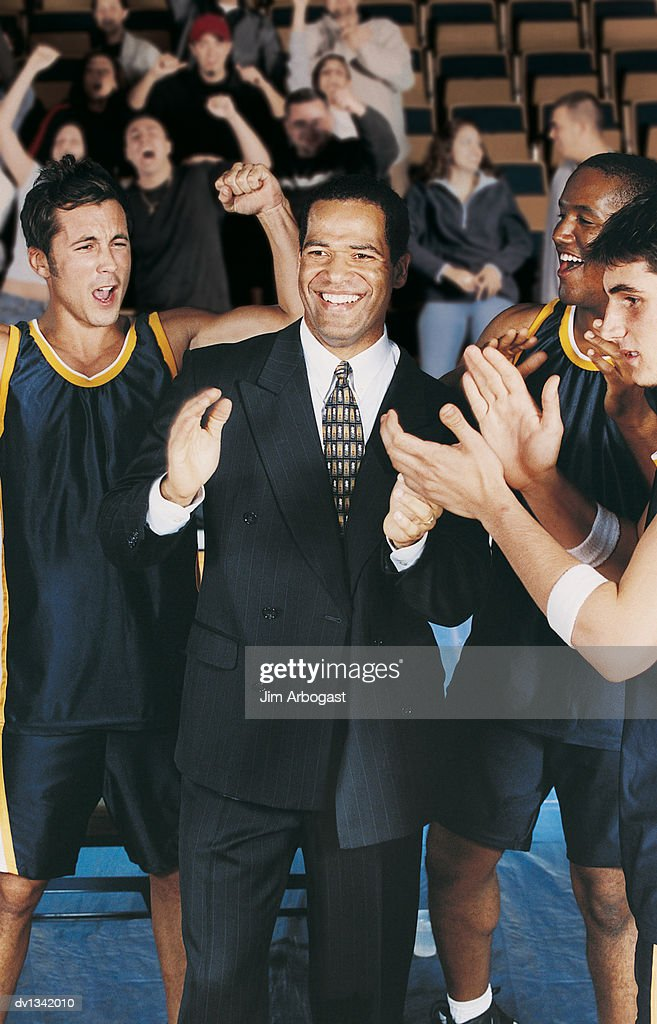 Basketball Players and Their Sports Coach Celebrating in a Basketball Court