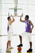 Basketball players high fiving on court