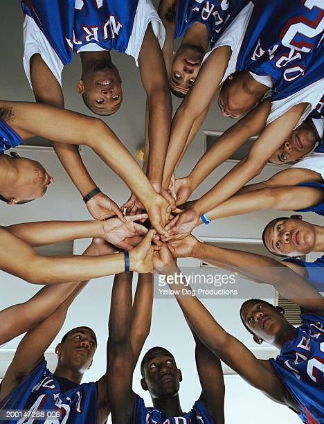 Basketball players (16-18) in huddle before game, view from below