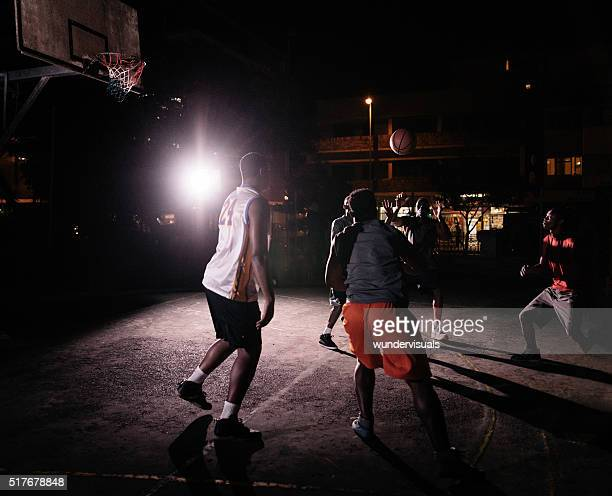 Basketball Players Playing in Court During Nighttime