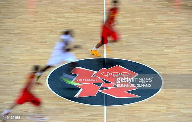 Basketball players run over the logo of the London 2012 Games during the Men's Preliminary Round Group B match Spain vs China at the London 2012...