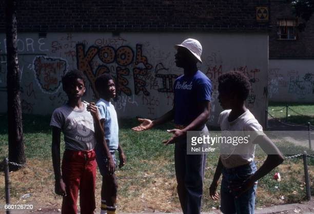 Portrait of Kansas CityOmaha Kings 'Tiny' Nate Archibald with local youth outside of his former South Bronx housing project apartment at Lester...
