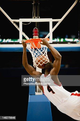 Basketball slam dunking, rear view