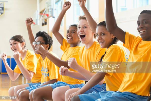 Basketball team cheering in gym