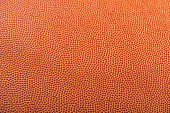 A close-up with selective focus on a basketball's pebbled textured.