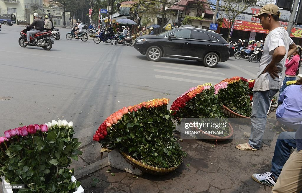 Baskets of roses are on sale at a street corner as Vietnamese celebrate the International Women's Day in Hanoi on March 8, 2013. The day is a good business opportunity for florists with a sharp rise of flowers's prices, especially for roses. AFP PHOTO/HOANG DINH Nam