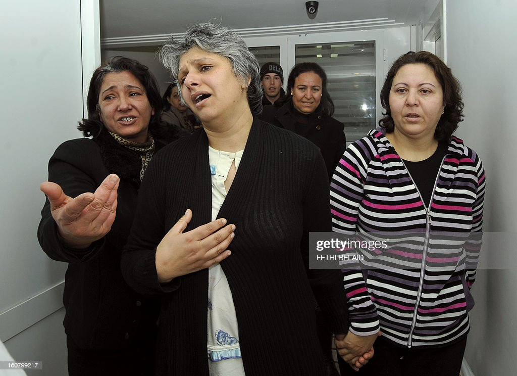 Basma Khalfaoui Belaid (C), the wife of assassinated Tunisian opposition leader and outspoken government critic Chokri Belaid, mourns over the latter's death after he was shot dead with bullets fired from close range on February 6, 2013, at a clinic in Tunis. President Moncef Marzouki has cancelled his participation in the Organisation of Islamic Cooperation summit in Cairo and is heading back to Tunisia after the murder of opposition leader Chokri Belaid, the presidency said. His assassination comes at a time when Tunisia is witnessing a rise in violence fed by political and social discontent two years after the mass uprising that toppled the former dictator Zine El Abidine Ben Ali. AFP PHOTO / FETHI BELAID