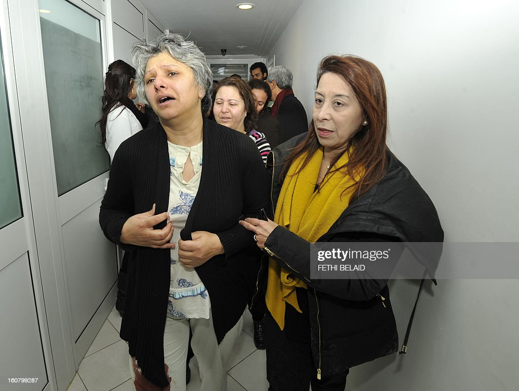 Basma Khalfaoui Belaid (L), the wife of assassinated Tunisian opposition leader and outspoken government critic Chokri Belaid, is seen wearing blood stained trousers as she is comforted by friends following her husband's death after he was shot dead with bullets fired from close range on February 6, 2013 at a clinic in Tunis. President Moncef Marzouki has cancelled his participation in the Organisation of Islamic Cooperation summit in Cairo and is heading back to Tunisia after the murder of opposition leader Chokri Belaid, the presidency said. His assassination comes at a time when Tunisia is witnessing a rise in violence fed by political and social discontent two years after the mass uprising that toppled the former dictator Zine El Abidine Ben Ali. AFP PHOTO / FETHI BELAID