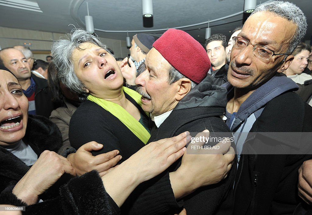 Basma Khalfaoui Belaid, wife of assassinated Tunisian opposition leader and outspoken government critic Chokri Belaid mourns with Chokri's father after his killing on February 6, 2013, at a clinic in Tunis. Belaid was gunned down outside his home in Tunis, sparking angry protests by his supporters and attacks on offices of the ruling Islamist Ennahda party. AFP PHOTO / FETHI BELAID