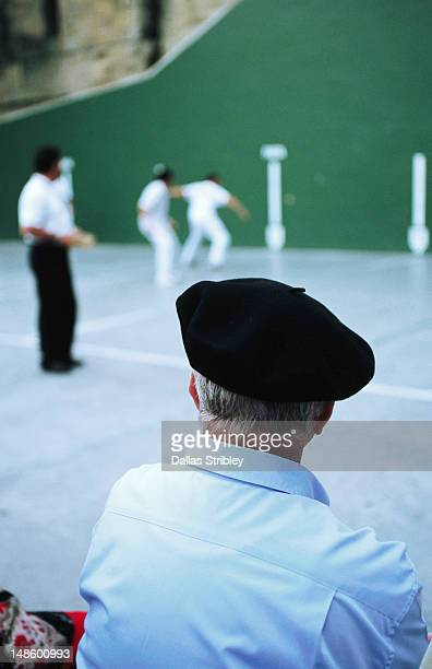 Basque man in beret watching game of pelota in Plaza de la Trinidad.