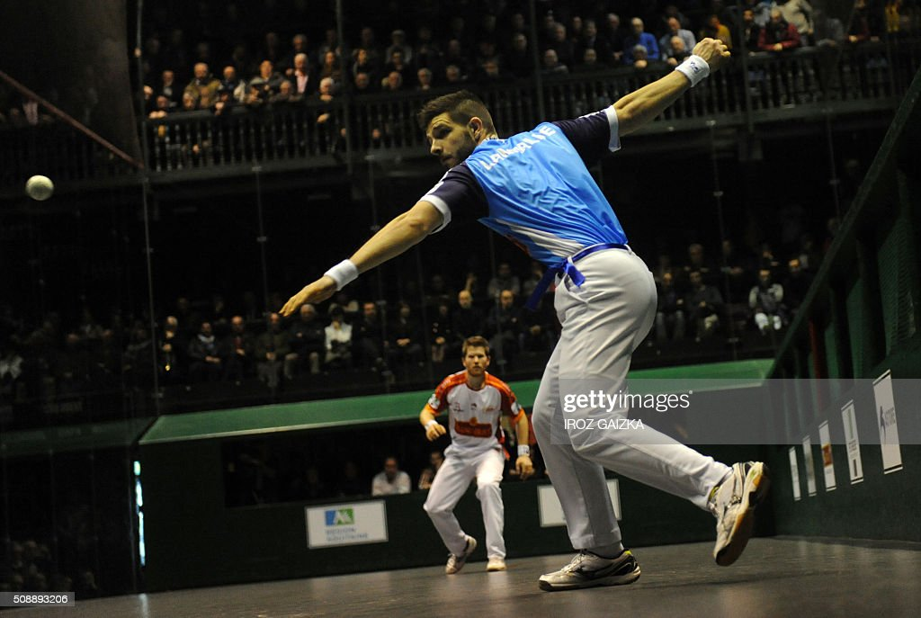 Basque pelota champions Peio Larralde (blue) and Baptiste Ducassou compete against each other during the final of the Hand Pelota French Championships, on February 7, 2016 in Bayonne. / AFP / IROZ GAIZKA