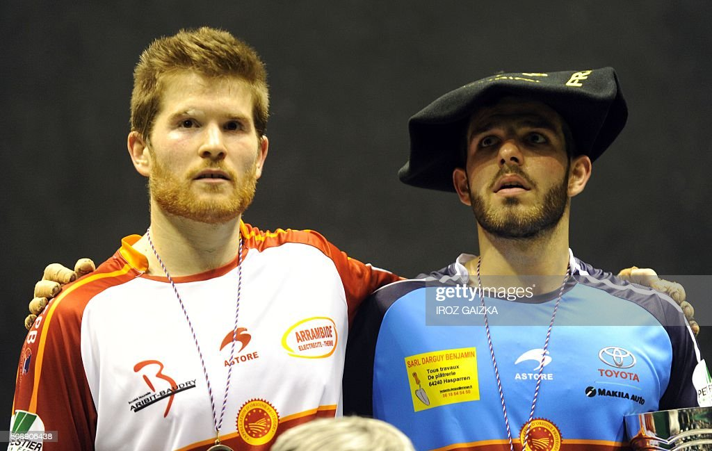 Basque pelota champions Peio Larralde (blue, winner) and Baptiste Ducassou (runner-up) pose on the podium after competing against each other in the final of the Hand Pelota French Championships, on February 7, 2016 in Bayonne. / AFP / IROZ GAIZKA