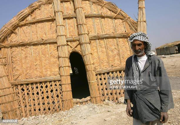 A Marsh Arab poses outside a traditional reed habitation in Abu al Muhammen just outside Basra in southern Iraq 16 October 2005 as millions of...
