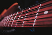 Close up shot of the neck of a bass guitar, the frets, and its steel strings.
