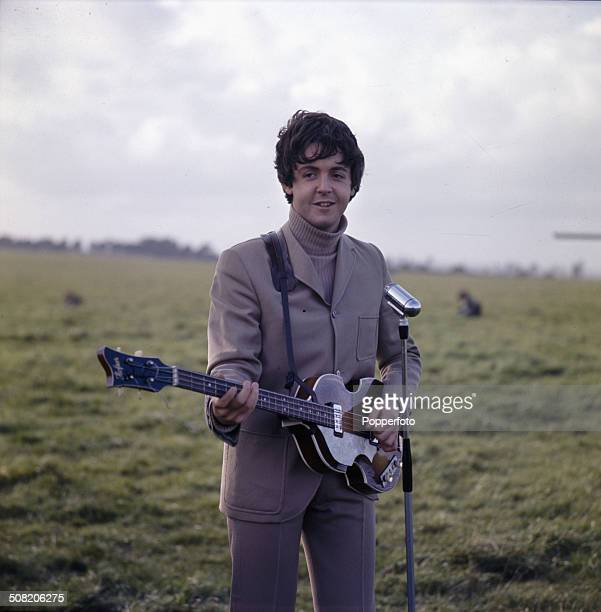 Bass guitarist Paul McCartney from The Beatles pictured playing his Hofner violin bass guitar on Salisbury Plain in England during the filming of...