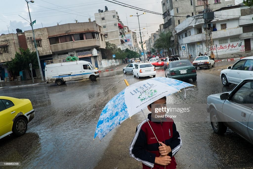 Bassam Farwan, 11, crosses the busy road in the rain as life in Gaza returns to normal, in Gaza City Gaza on November 22, 2012. The streets were filled with cars and pedestrians.