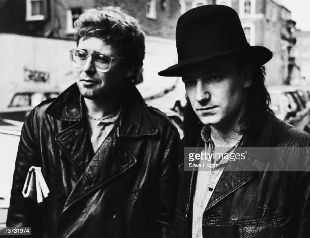 U2 bassist Adam Clayton and singer Bono walking down a street 1985
