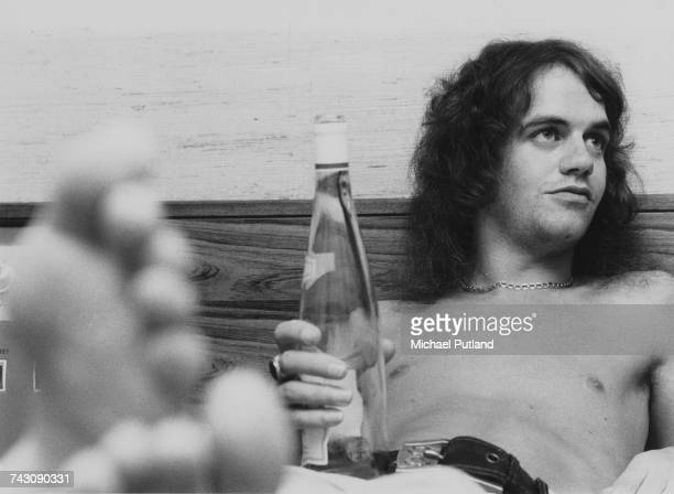 Bassist and fiddle player Jim Lea of English glam rock group Slade pictured holding a bottle of white wine in a hotel room in the United Kingdom in...