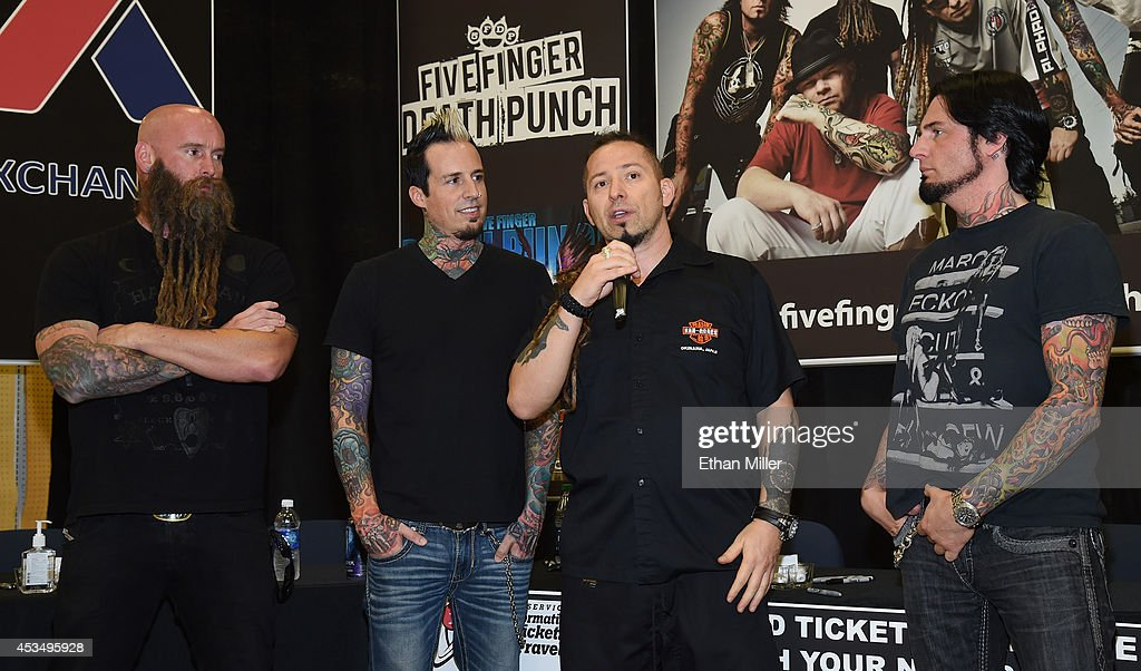 Bassist Chris Kael, drummer Jeremy Spencer, and guitarists Zoltan Bathory and Jason Hook of Five Finger Death Punch speak at Nellis Air Force Base as the band highlights its campaign to raise awareness about veterans suffering from post-traumatic stress disorder (PTSD), in part by launching the video 'Wrong Side of Heaven,' that deals with the subject on August 11, 2014 in Las Vegas, Nevada.