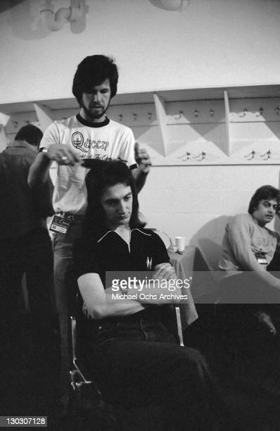 Bassist John Deacon of British rock band Queen has his hair done backstage before a concert circa 1977