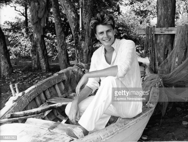 Bassist John Taylor of the British pop group Duran Duran smiles while posing in a dry docked fisherman's boat probably on location for a video shoot...
