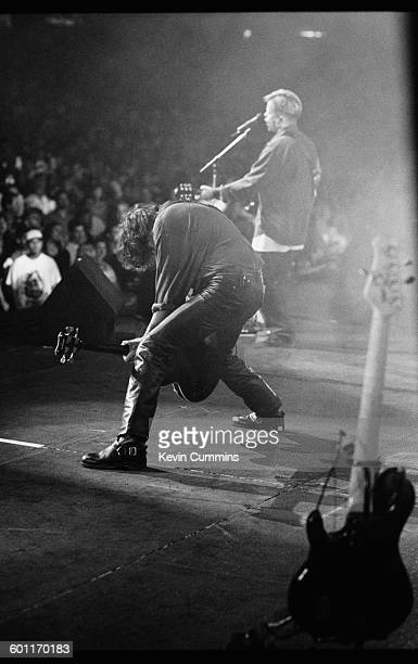 Bassist Peter Hook and singer/guitarist Bernard Sumner performing with English rock group New Order during the band's North American tour JulyAugust...