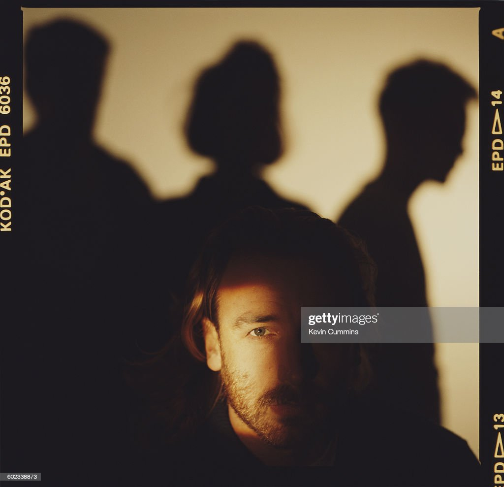 Bassist Peter Hook of English rock group New Order, 1st November 1985. Other group members are silhouetted behind him.