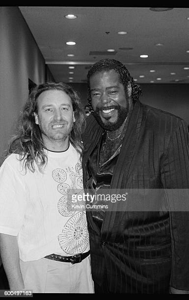 Bassist Peter Hook of English rock group New Order with American soul singer Barry White New York City July 1990