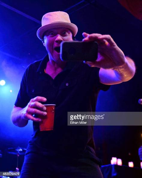 Bassist Vince Hornsby of Sevendust takes a photo with a cell phone as he performs during an acoustic concert at the Marquee Theatre as the band tours...