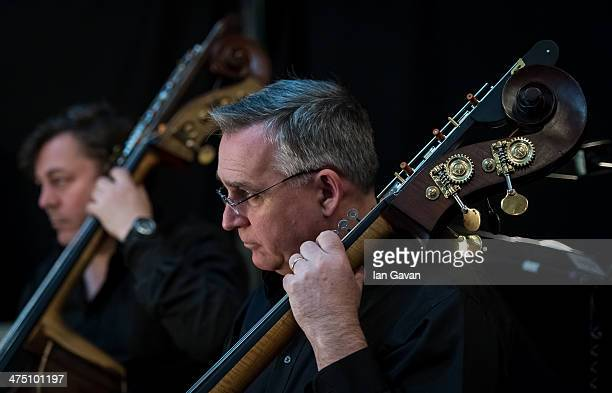Bassists prepare in the orchestra pit ahead of a dress rehearsal for Puccini's 'La Boheme' at Royal Albert Hall on February 26 2014 in London England
