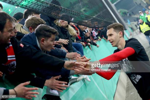 Bastian Oczipka of Frankfurt celebrates with the fans after winning the penalty shoot out during the DFB Cup semi final match between Borussia...