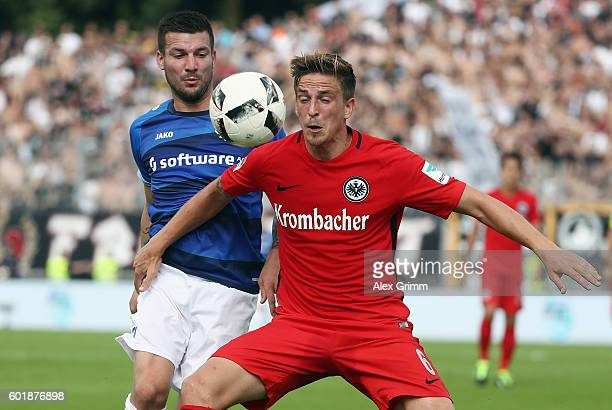 Bastian Oczipka of Frankfurt is challenged by Jerome Gondorf of Darmstadt during the Bundesliga match between SV Darmstadt 98 and Eintracht Frankfurt...