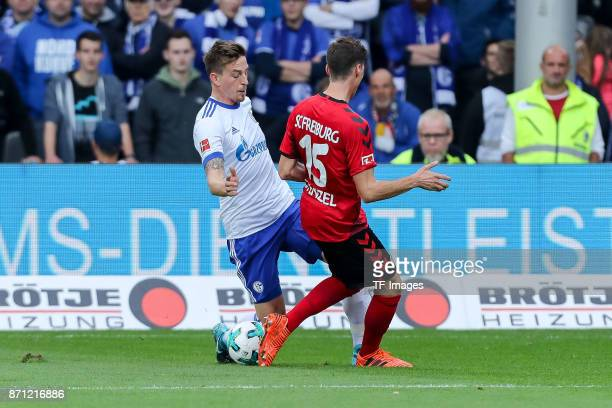 Bastian Oczipka of Schalke and Pascal Stenzel of Freiburg battle for the ball during the Bundesliga match between SportClub Freiburg and FC Schalke...