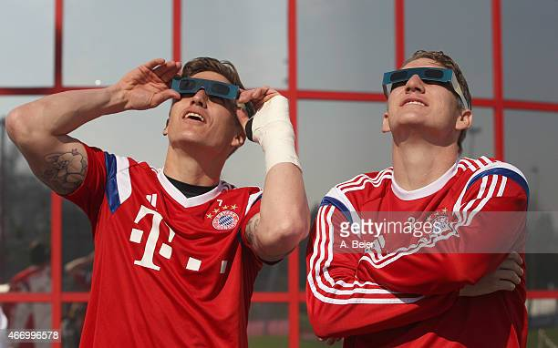 Bastian Schweinsteiger and his brother Tobias Schweinsteiger of Bayern Muenchen watch a penumbral solar eclipse before a training session at the FC...