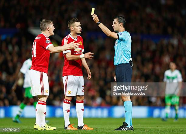 Bastian Schweinsteiger and Morgan Schneiderlin of Manchester United react as referee Viktor Kassai shows a yellow card during the UEFA Champions...