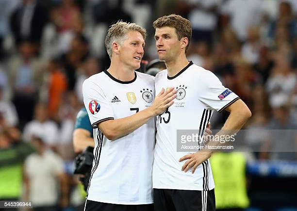 Bastian Schweinsteiger and Thomas Mueller of Germany console each other after defeat in the UEFA EURO semi final match between Germany and France at...