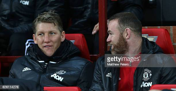 Bastian Schweinsteiger and Wayne Rooney of Manchester United watch from the bench during the Premier League match between Manchester United and West...