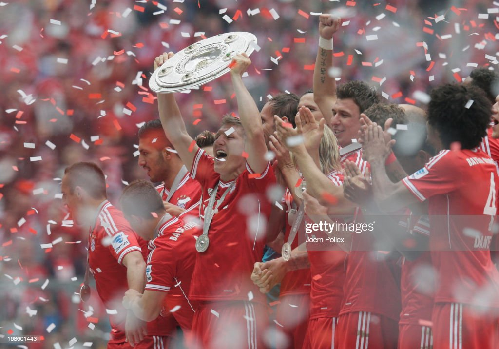 <a gi-track='captionPersonalityLinkClicked' href=/galleries/search?phrase=Bastian+Schweinsteiger&family=editorial&specificpeople=203122 ng-click='$event.stopPropagation()'>Bastian Schweinsteiger</a> celebrates with FC Bayern Muenchen team mates as they receive the championship trophy after the Bundesliga match between FC Bayern Muenchen and FC Augsburg at the Allianz Arena on May 11, 2013 in Munich, Germany.