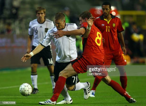 Bastian Schweinsteiger is challenged by Jan Vertonghen of Belgium during the EURO 2012 Group A Qualifier match between Belgium and Germany at Roi...