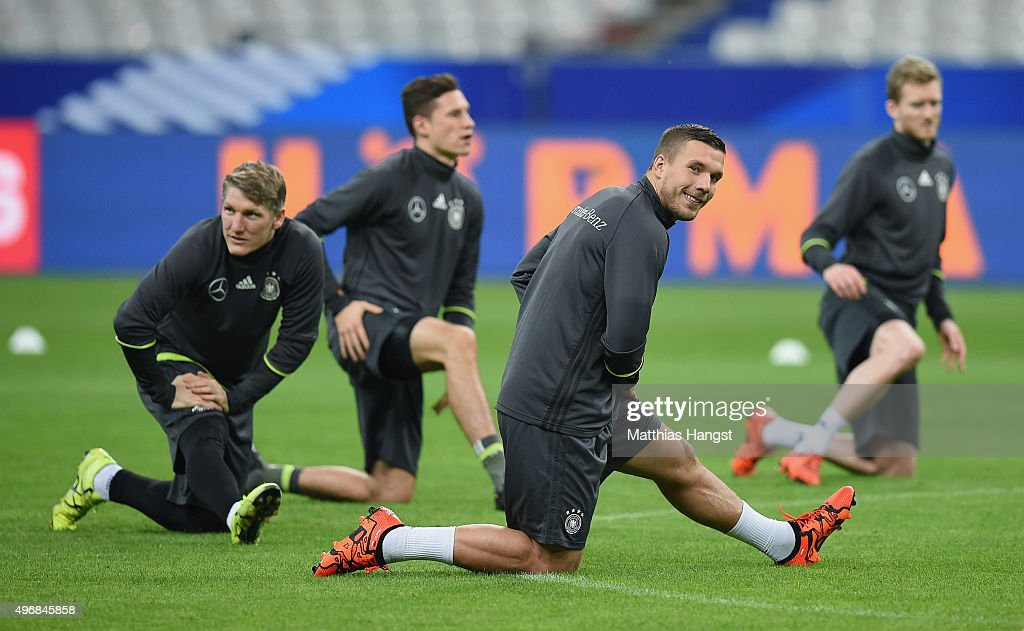 Bastian Schweinsteiger, Julian Draxler and Lukas Podolski of Germany stretch during a Germany training session ahead of their International Friendly against France at Stade de France on November 12, 2015 in Paris, France.