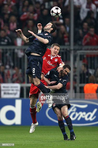 Bastian Schweinsteiger of Bayern jump for a header with Miralem Pjanic and Lisandro of Lyon during the UEFA Champions League semi final first leg...