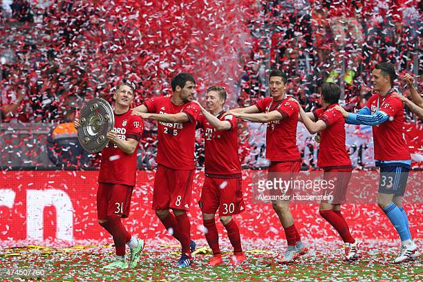 Bastian Schweinsteiger of Bayern Muenchen and teammates celebtrate with the trophy after winning the league during the Bundesliga match between FC...