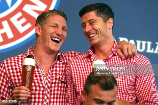 Bastian Schweinsteiger of Bayern Muenchen attends with his team mate Robert Lewandowski the FC Bayern Muenchen Paulaner photo shoot in traditional...