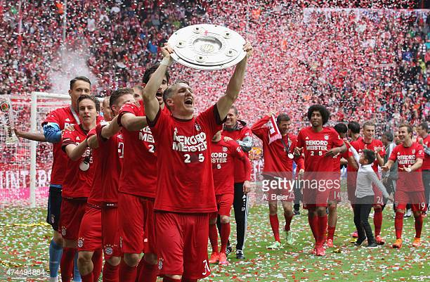 Bastian Schweinsteiger of Bayern Muenchen celebrates winning the German Championship with the Bundesliga trophy after the Bundesliga match FC Bayern...