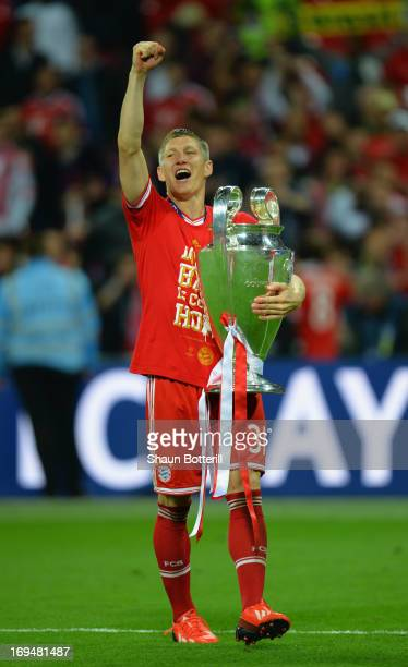 Bastian Schweinsteiger of Bayern Muenchen holds the trophy after winning the UEFA Champions League final match against Borussia Dortmund at Wembley...