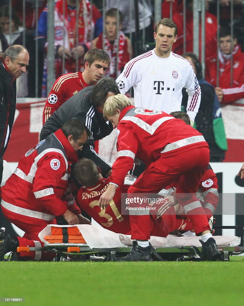 Bastian Schweinsteiger of Bayern Muenchen is laid down on a stretcher as teammates Philipp Lahm (3rdL) and goalkeeper Manuel Neuer (topR) watch him during the UEFA Champions League Group A match between FC Bayern Muenchen and SSC Napoli at Allianz Arena on November 2, 2011 in Munich, Germany.