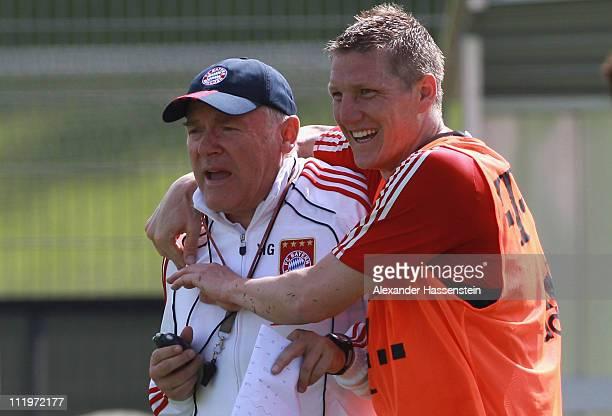Bastian Schweinsteiger of Bayern Muenchen jokes with assistent coach Hermann Gerland during the Bayern Muenchen training session at Bayern's training...